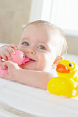 Portrait of baby girl (9-12 months) in bathtub, close-up